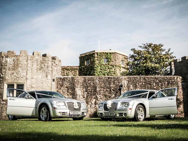 two decorated luxury wedding cars outside a venue near Bristol UK